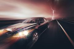 Speeding Compact Car and the Storm. Car on the Highway. Stock Photos