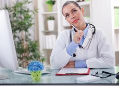 Serious  modern young female doctor in the office Stock Photos