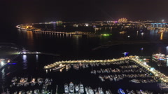 Palm Jumeirah with yahcts in harbor and Atlantis hotel at night general view Stock Footage