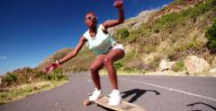 African American teen girl on a longboard doing downhill racing Stock Footage