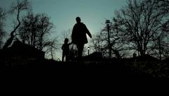 Silhouette of man and child. Father and little daughter walking in park. Sun. Stock Footage
