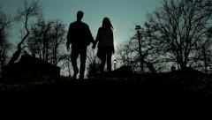 Silhouette of young couple who walking in park, holding hands, love, sunny day. - stock footage