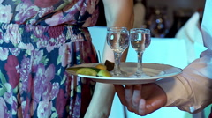 Hand of the waiter with a glasses of vodka on a plate. - stock footage