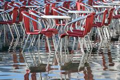 Venice, chairs of the outdoor cafes with water at high tide - stock photo