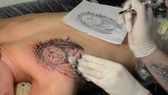 Tattoo artist doing a dream catcher tattoo Stock Footage