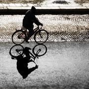 Back lit cyclist - stock photo