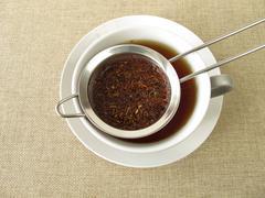 Rooibos tea in tea strainer Stock Photos