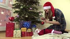 Mother show newborn daughter in christmas dress fir toy ball Stock Footage