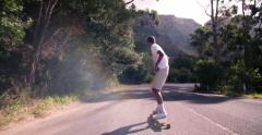 Longboarder skating downhill on mountain road Stock Footage