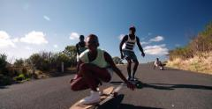 Mixed racial group of teen skateboarders racing downhill together Stock Footage