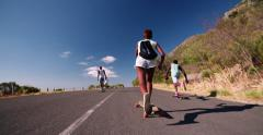 Skater girl downhill racing on her longboard with friends Stock Footage