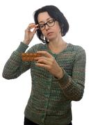 Woman  in  glasses looks at medicament - stock photo