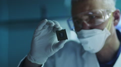 Computer Engineer is Holding and Inspecting Processor Chip Stock Footage