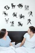 Man and surprised woman in bedroom surrounded looking up at horoscope Stock Photos