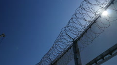 Pan of razor wire atop the US Border at Otay Mesa Stock Footage