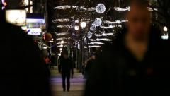 Frontal shot of people in a pedestrian zone at night with Christmas decorations Stock Footage