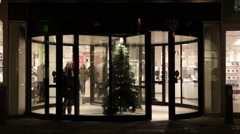 Revolving door to a store at Christmas time Stock Footage