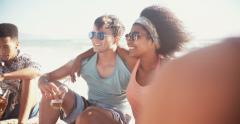 Mixed race couple drinking beer on the beach on a summer day Stock Footage