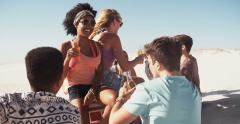 Smiling Afro girl hanging with friends on the beach Stock Footage