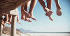 Legs of friends sitting on a beach boardwalk together Stock Footage