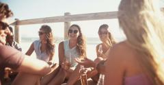 Group of friends relaxing and drinking beer at the beach Stock Footage