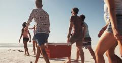 Friends on a beach carrying cooler box for a party - stock footage
