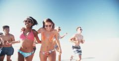 Group of friends of mixed races running on the beach together Stock Footage