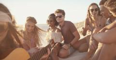 Friends at a sunset beachparty with a guitar Stock Footage