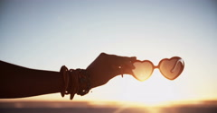 Hand holding heart-shaped sunglasses on a beach at sunset Stock Footage