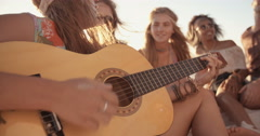Girl playing her guitar on the beach with friends Stock Footage