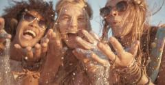 Girls blowing confetti from hands on beach in Slow Motion Stock Footage