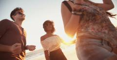 Afro girl dancing with her boyfriend at a sunset beachparty - stock footage