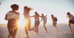 Young friends walking on a beach at sunset Stock Footage