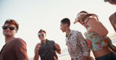 Friends dancing at a summer sunset beachparty Stock Footage