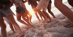 Legs of youth dancing on the beach at sunset - stock footage