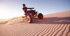 Quad biker in desert race with sun flare behind Stock Footage