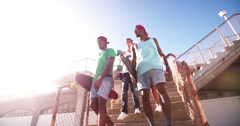 Cool teen skater friends walking together with clear sky overhead - stock footage