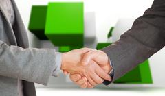 Stock Illustration of Composite image of two people having a handshake in an office