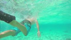 UNDERWATER: Man swimming in crystal clear Indian Ocean Stock Footage