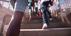 Teenagers wearing sneakers coming up steps in an urban setting Stock Footage