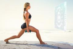 Composite image of fit blonde doing weighted lunges on the beach - stock photo