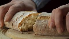 Static view of mans hands tearing loaf of bread in half Stock Footage
