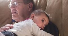 Tired elderly man holding young baby - stock photo