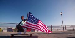 African American longboarder flying an American flag Stock Footage