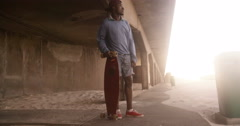 Stock Video Footage of Afro american teenage guy standing under overpass with longboard