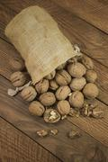 Nuts in a burlap pouch on wooden boards Stock Photos