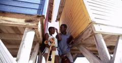 Teen African American couple with colorful wooden buildings Stock Footage
