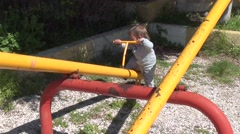Baby can hardly get out from seesaw Stock Footage