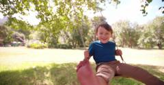 Delighted little boy swinging in sunny natural park Stock Footage