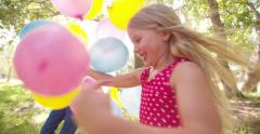Friendly happy children having fun with balloons outdoors Stock Footage